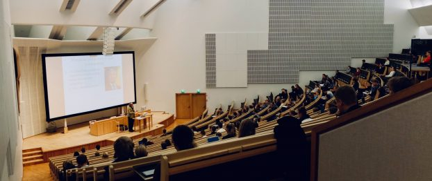 a man speaking in an auditorium with an audience