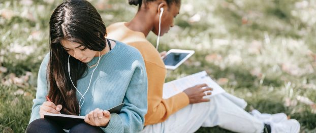 two college girls studying and listening to music in the forest