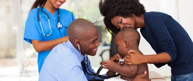 a doctor checking a baby accompanied by his mother and nurse